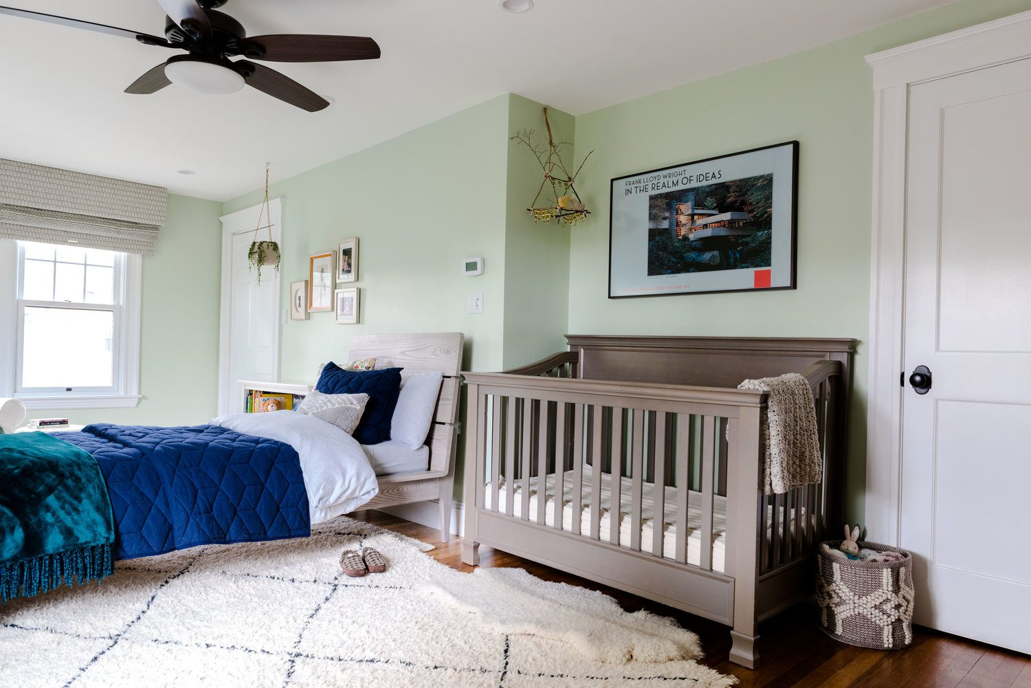 finished brothers bedroom with mint green walls behind dark wood crib