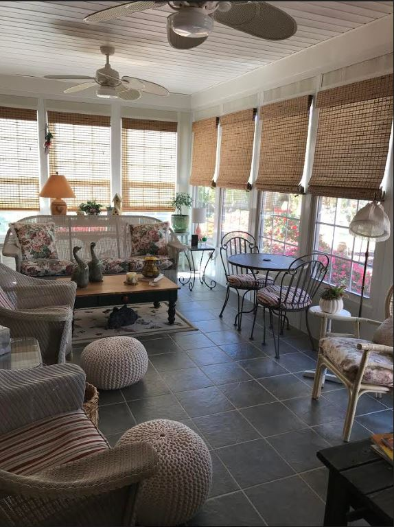 Select Blinds woven wood shades over many windows in living area