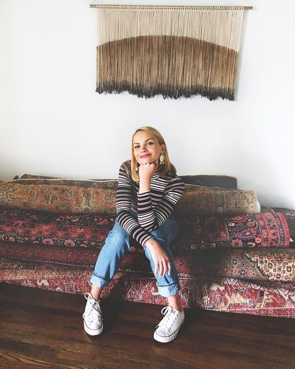 Chef and Select Blinds Inspiring Decorator Monique Volz sitting on antique rugs on hardwood floor. Photo by Ambitious Kitchen.
