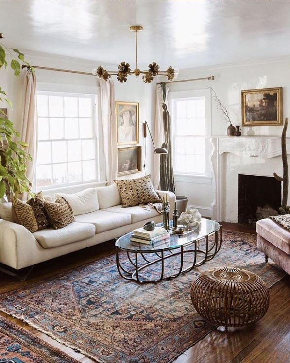 Antique area rug among white living room furniture and drapery accented by green foliage, photo by Carley Summers
