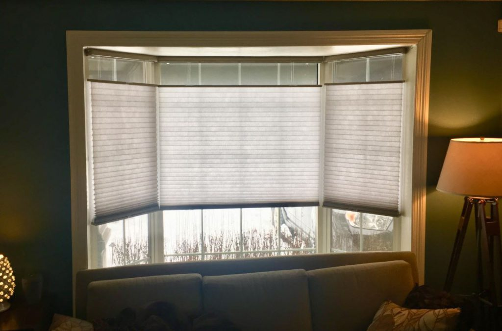 Signature Light Filtering Cordless Top Down Bottom Up Cellular Shades in Taupe hang in bay window