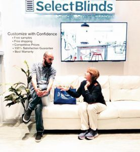 Jamie Y. of Select Blinds talks on couch in booth Atlanta home and garden show
