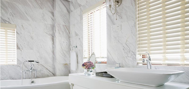 Venetian blinds over claw foot tub and sink in all white marble bathroom
