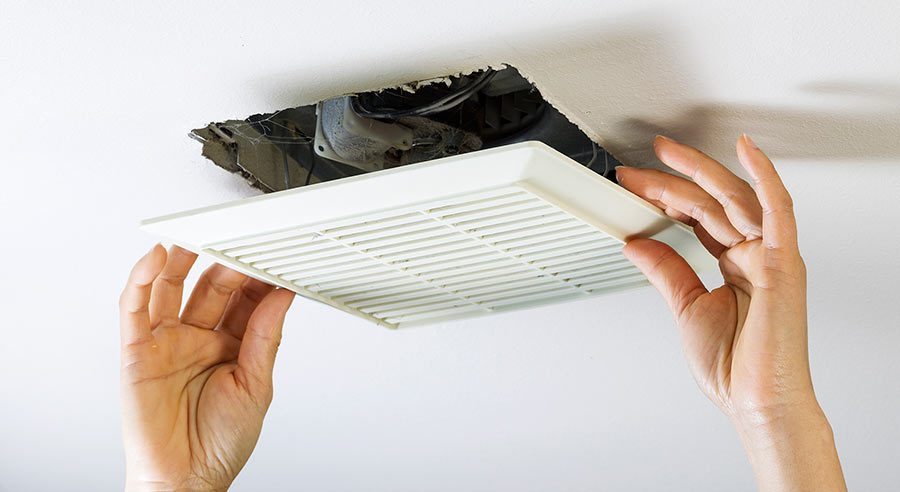 Hands removing white bathroom exhaust fan faceplate