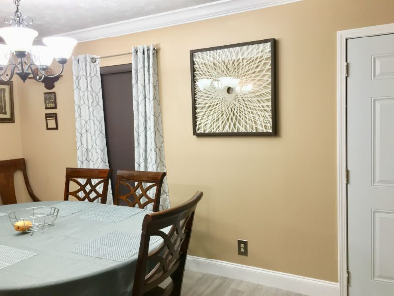 White flowery wall art near window with Select Blinds roller shades and custom drapery