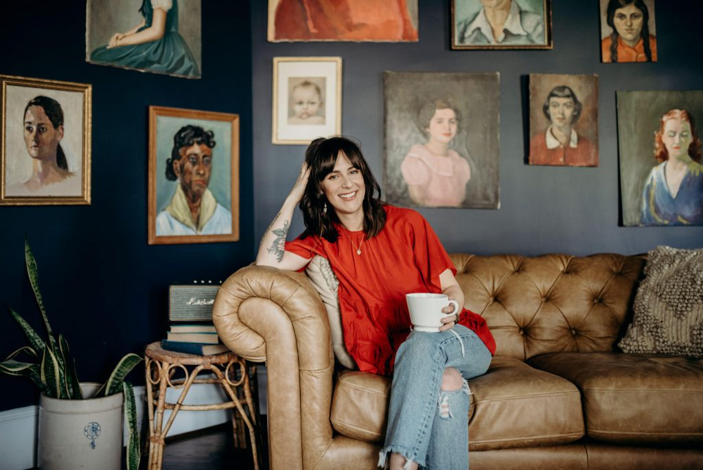 Audrey sprinkle sits on leather couch in front of paintings of women