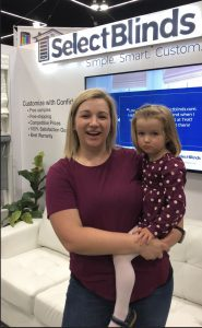 Customer holds daughter in Select Blinds booth