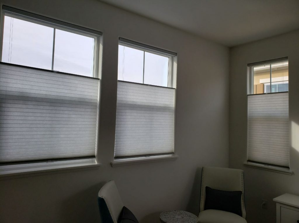White Cellular honeycomb shades in living room windows