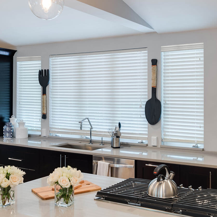 Beautiful black and white kitchen with white blinds.