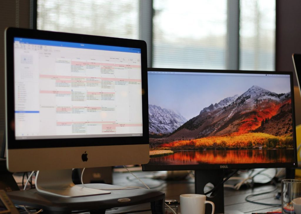 Dual monitors showing calendar and mountain background.