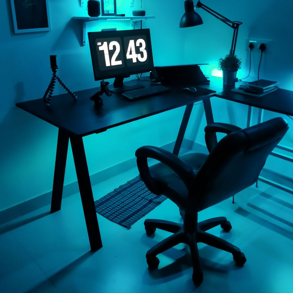 Dark office with blue lighting and large clock on the monitor.