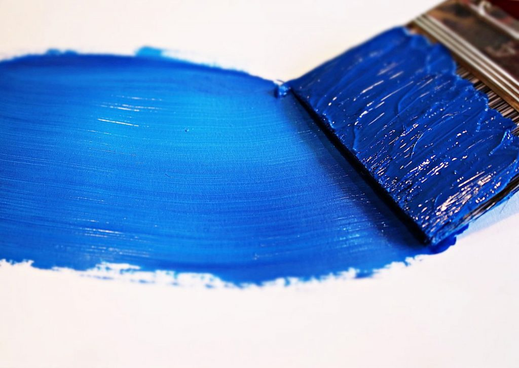 Blue paint and paintbrush on a white background.