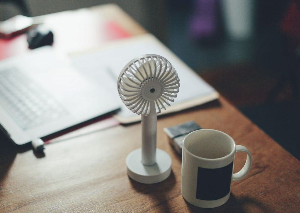 Small portable desk fan next to a laptop.