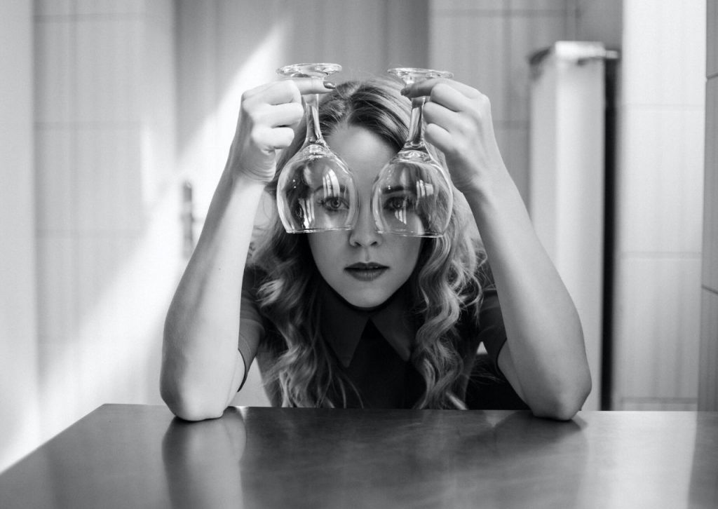 Woman looking through two wine glasses.