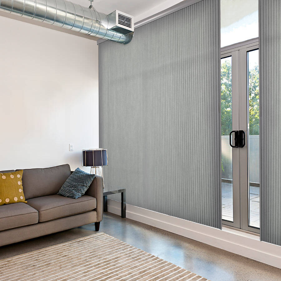 Light grey vertical honeycomb cellular blinds covering a patio door.