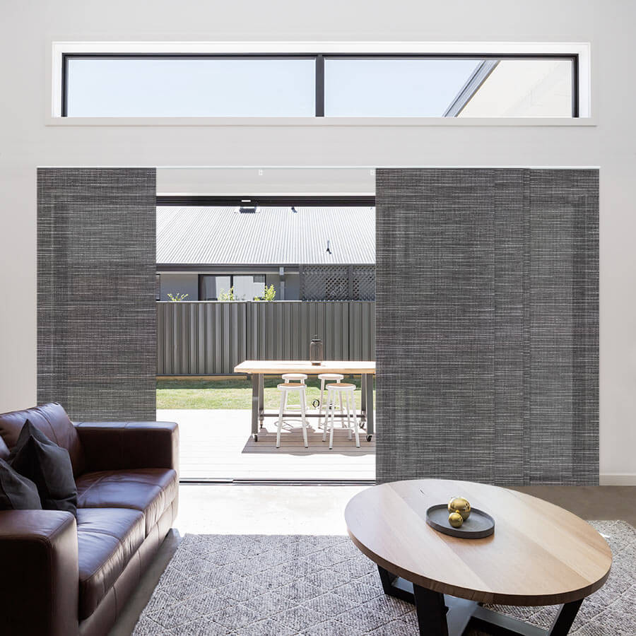 Dark grey solar panel track blinds covering a wide patio door.