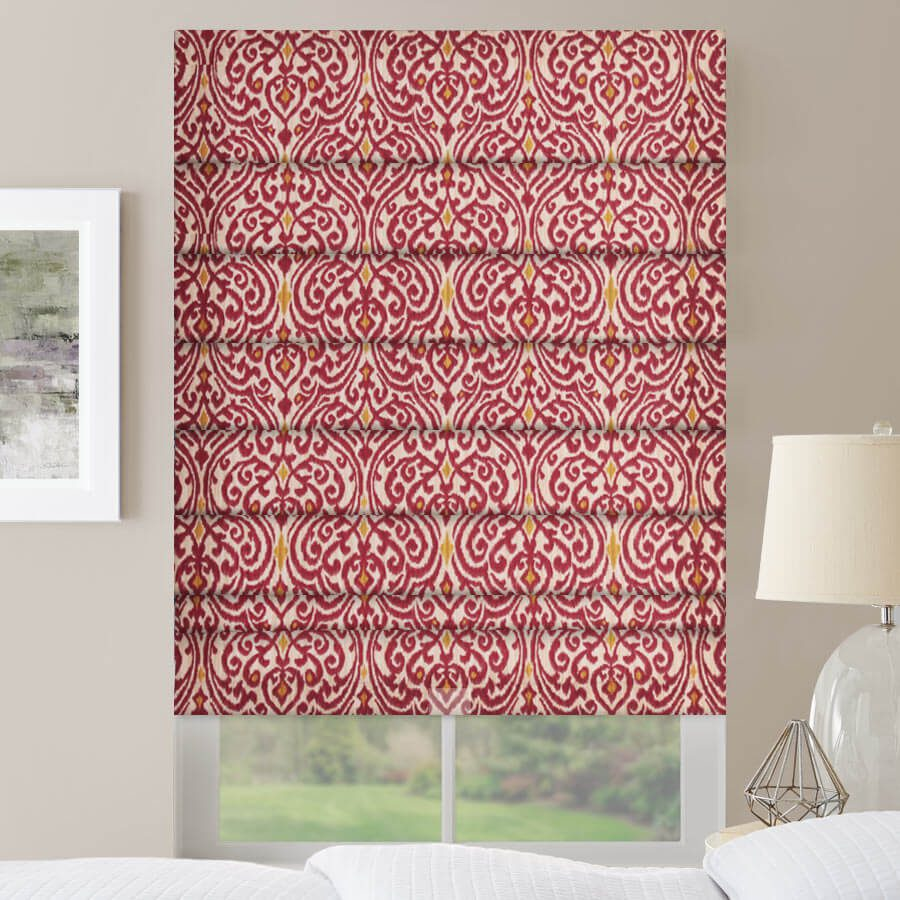 Roman shades with an intricate red pattern in a bedroom.