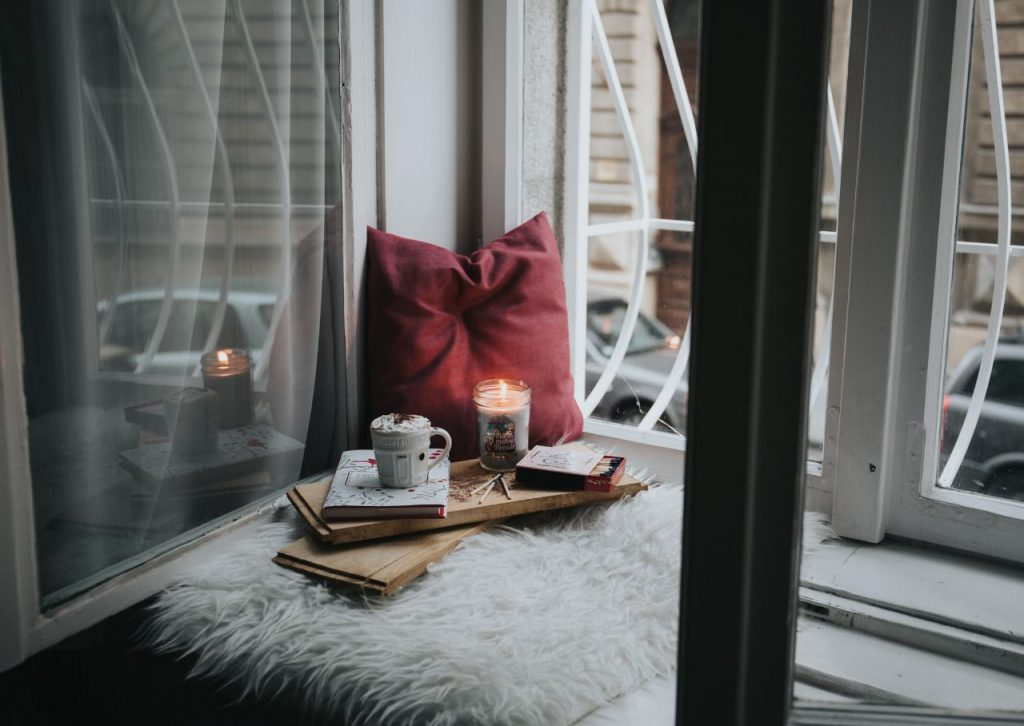 Red pillow and hot cocoa on a window sill.