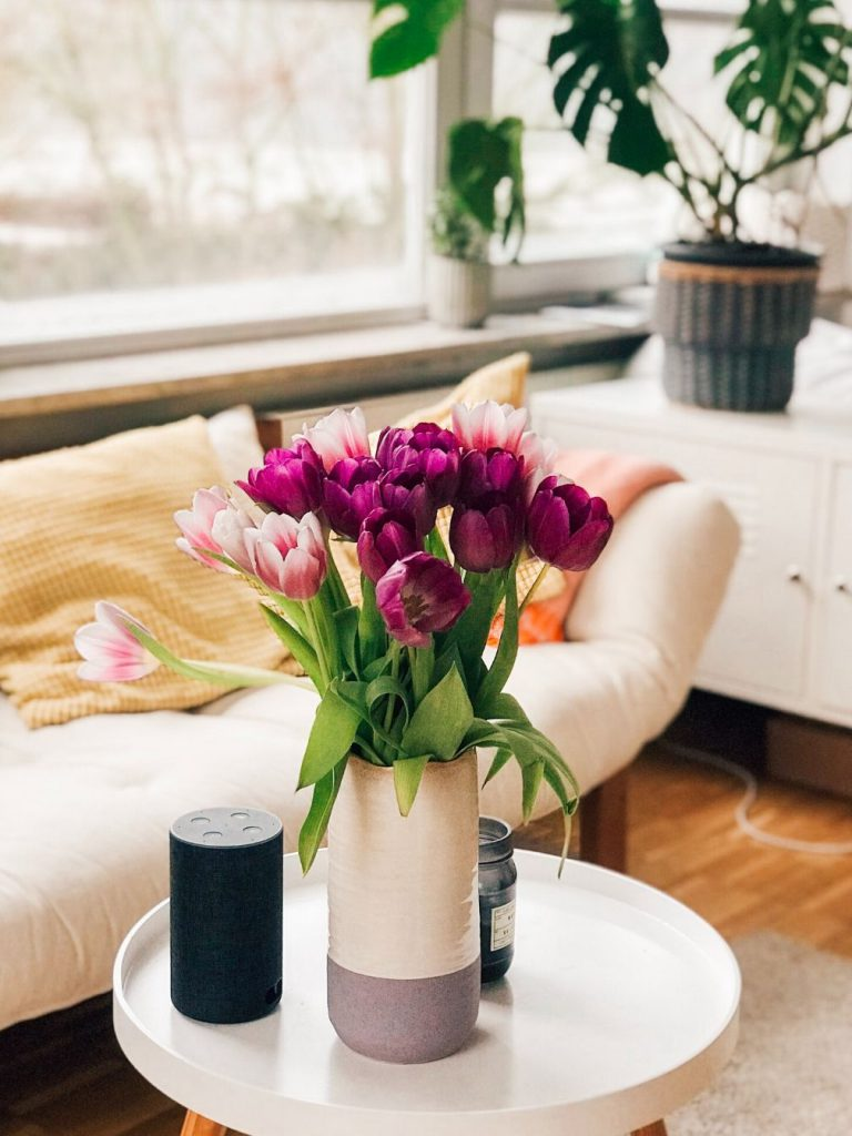 Purple and pink tulips on a table next to a couch.