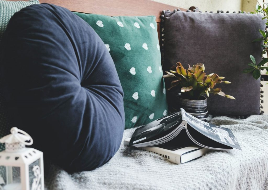 Blue and green throw pillows on a couch with books.