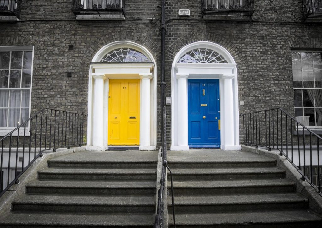 Two brownstones with yellow and blue painted front doors.