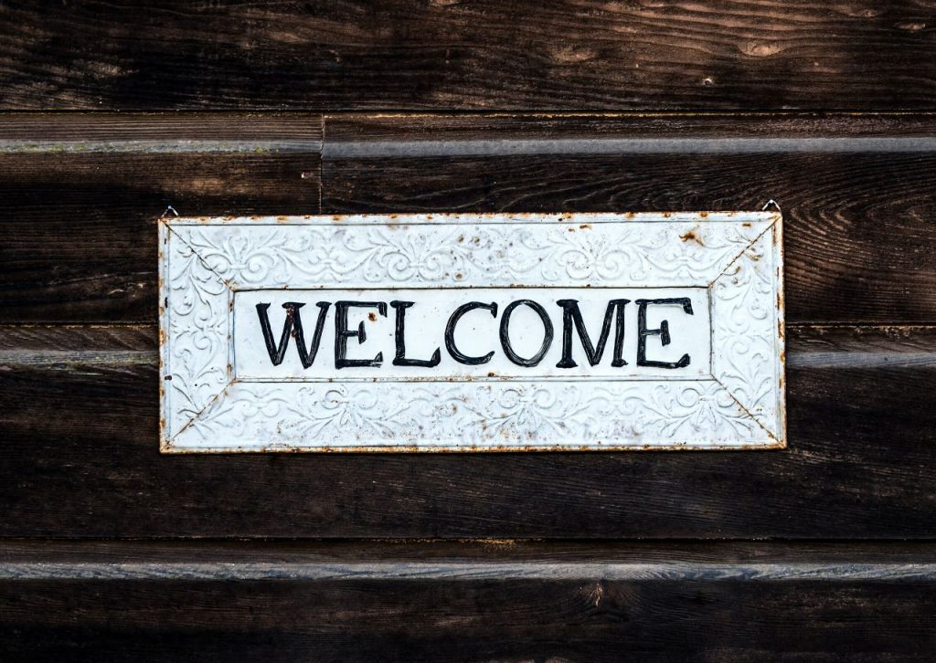 Black and white welcome sign hung on a stained wood door.