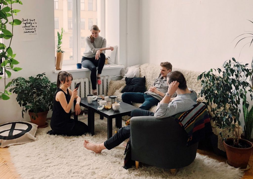 Four people hanging out in a living room with a shag rug.