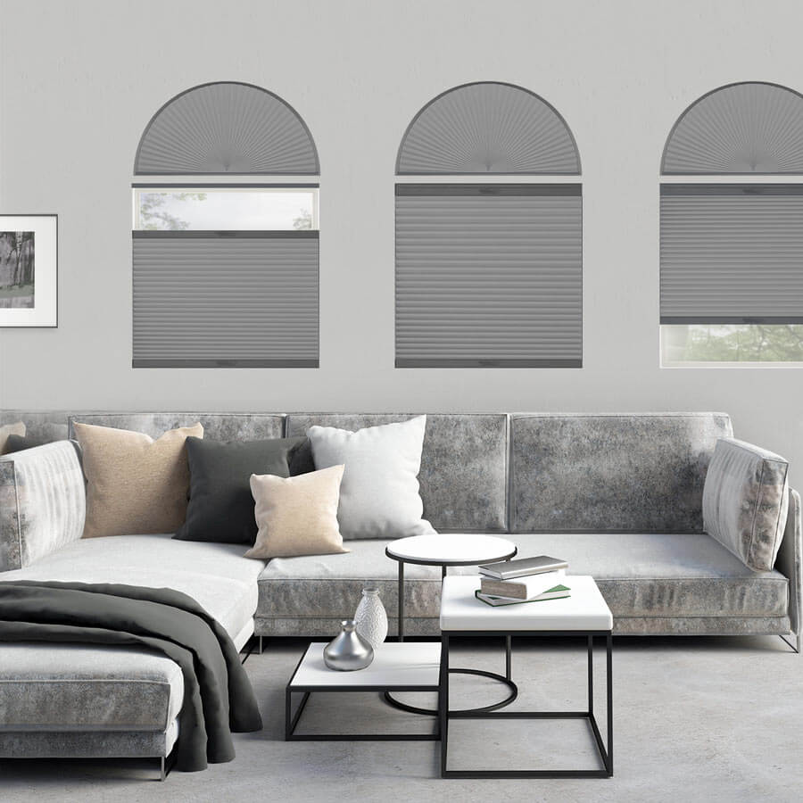 Grey honeycomb shades and arch coverings in a grey themed living room.