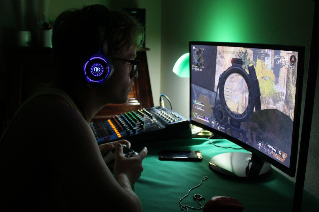 Gamer playing a video game in a darkened gaming room.